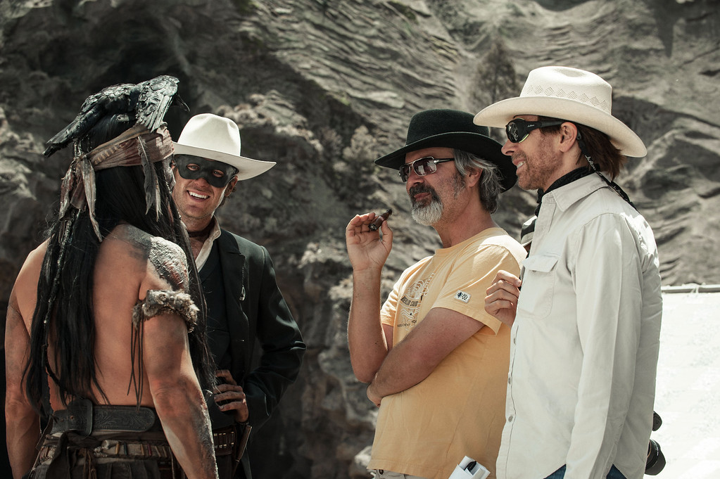 """. This undated publicity photo released by Disney/Bruckheimer Films shows, from left, Johnny Depp as Tonto, Armie Hammer as The Lone Ranger, director, Gore Verbinski and producer, Jerry Bruckheimer, on the set of \""""The Lone Ranger.\"""" The film opens nationwide on July 3, 2013. (AP Photo/Disney/Bruckheimer Films, Peter Mountain)"""
