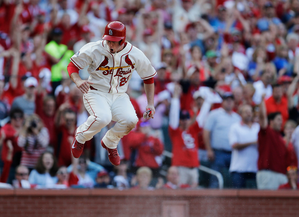 . St. Louis Cardinals\' David Freese jumps over home plate after scoring from third on a sacrifice fly by Jon Jay during the fifth inning of Game 2 of the National League baseball championship series against the Los Angeles Dodgers Saturday, Oct. 12, 2013, in St. Louis. (AP Photo/Jeff Roberson)