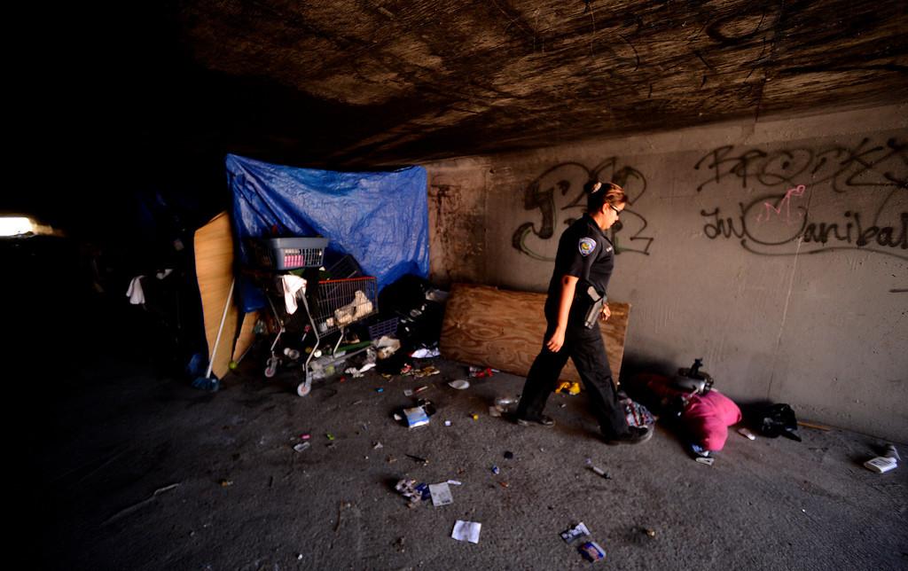 . San Bernardino Police Officer and Homeless Advocate Sochilt Martinez investigates a homeless camp located in the wash underneath 40th Street in San Bernardino August 14, 2013.  GABREL LUIS ACOSTA/STAFF PHOTOGRAPHER.