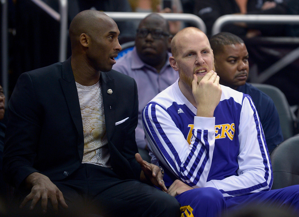 . Los Angeles Lakers guard Kobe Bryant, left, talks to center Chris Kaman on the end of the bench during the first half of an NBA basketball game against the Orlando Magic in Orlando, Fla., Friday, Jan. 24, 2014. (AP Photo/Phelan M. Ebenhack)