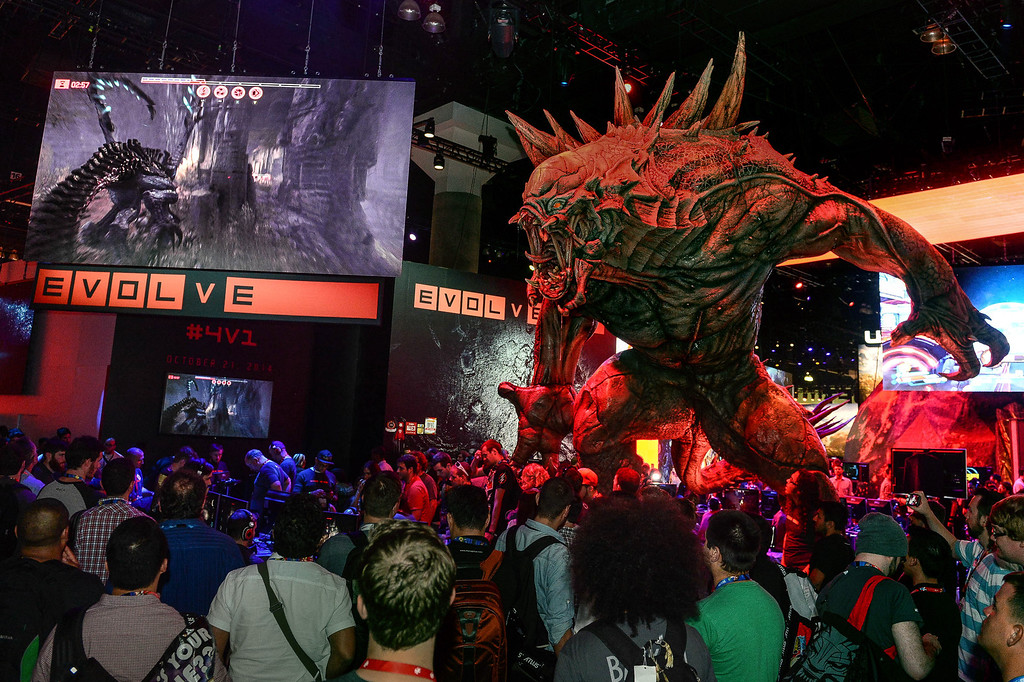 """. People stand next to a monster character from the video game \""""Evolve\"""" as they watch gamers play the video game at the Electronic Entertainment Expo in Los Angeles on Tuesday, June 10, 2014. (Photo by Watchara Phomicinda)"""
