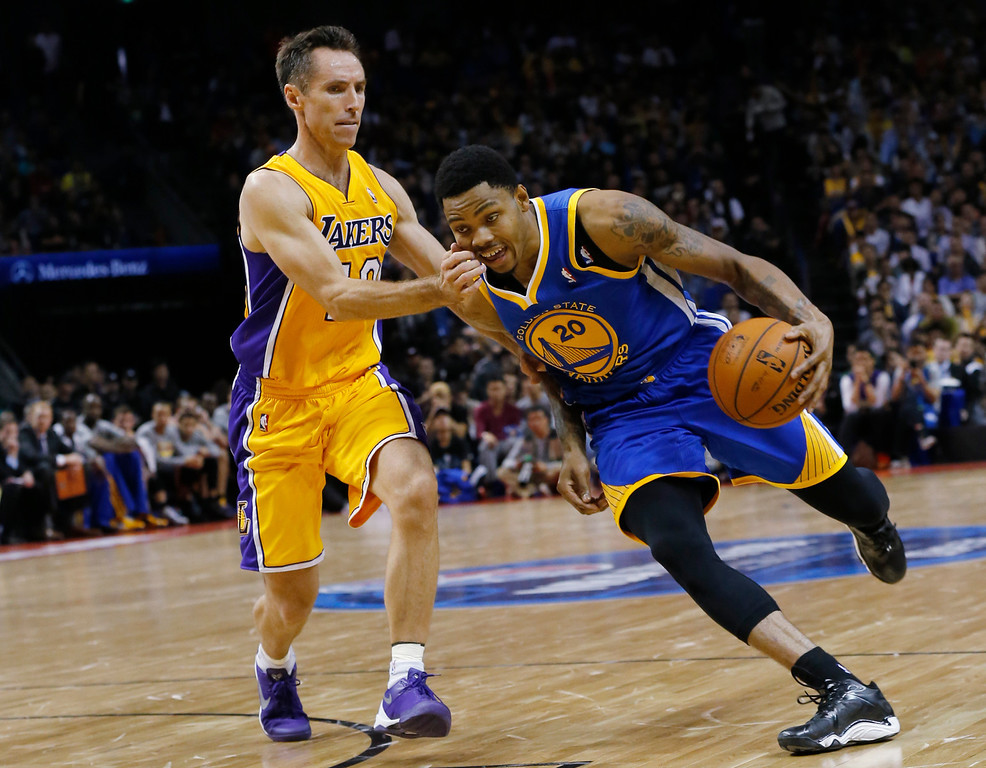 . Kent Bazemore of Golden State Warriors, right, dives against Steve Nash of Los Angeles Lakers, left, during a 2013-2014 NBA preseason game between Lakers and Warriors at Mercedes-Benz Arena in  Shanghai, China, Friday, Oct. 18, 2013. (AP Photo/Eugene Hoshiko)