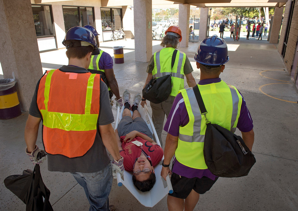 """. Diamond Bar High staff members carry an \""""injured\"""" student to triage during the Great ShakeOut earthquake drill at the Diamond Bar campus October 17, 2013.  (Staff photo by Leo Jarzomb/SGV Tribune)"""