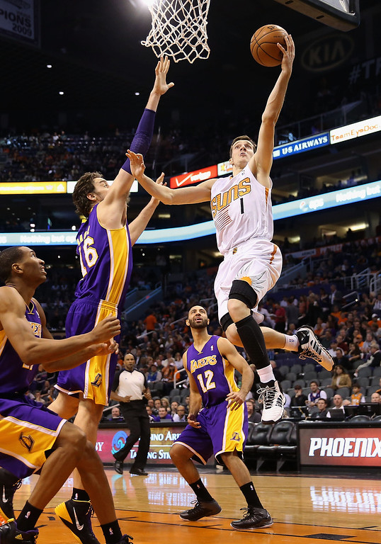 . Goran Dragic #1 of the Phoenix Suns lays up a shot past Pau Gasol #16 of the Los Angeles Lakers during the second half of the NBA game at US Airways Center on January 15, 2014 in Phoenix, Arizona. The Suns defeated the Lakers 121-114.    (Photo by Christian Petersen/Getty Images)