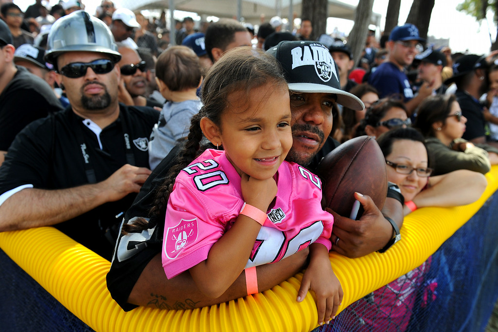. Brian Barber, of Oxnard, holds his daughter Kobianna Barber, 5, as they watch the Cowboys-Raiders practice in Oxnard, Wednesday, August 13, 2014. (Photo by Michael Owen Baker/Los Angeles Daily News)