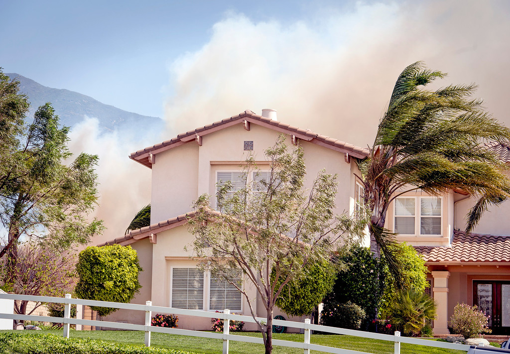 . Smoke from the Etiwanda Fire looms behind a home in the 5400 block of Carriage Place in Ranco Cucamonga, Calif. April 30, 2014.  (Staff photo by Leo Jarzomb/San Gabriel Valley Tribune)