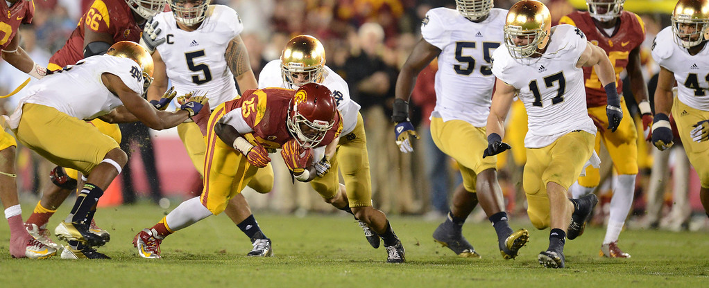 . USC\'s  Silas Redd (25) is dragged down by a host of Notre Dame defenders during their game at the Los Angeles Memorial Coliseum Saturday, November 24, 2012. Notre Dame beat USC 22-13. (Hans Gutknecht/L.A. Daily News)