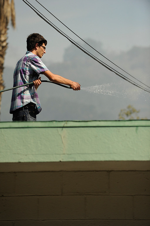 . A man uses a garden hose to water down the roof of a auto repair shop on East Chevy Chase Dr. A brush fire burned nearly 75 acres in an area north and east of the 134 and 2 freeways in Glendale. Residents on East Chevy Chase, east of the 2 freeway were evacuated as helicopters, hand crews and firefighters battled the fire that burned through the mountains and canyons. Glendale, CA 5/3/2013(John McCoy/Staff Photographer)