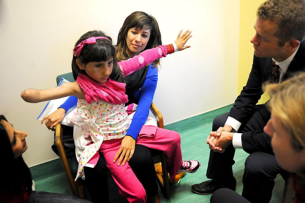 ". ""Shabibi\"" demonstrates her arm movement for Plastic and Reconstructive Surgeon Dr. William Magee and Orthapaedic Surgeon Anna Cuomo at the Shriners Hospital for Children in Los Angeles, CA December 13, 2013.  Shabibi is one of two Afghan children who were injured by bomb and grenade blasts who have been brought to the U.S. by the Los Angeles-based organization Children of War Foundation and will be receive treatment at the hospital.(Andy Holzman/Los Angeles Daily News)"