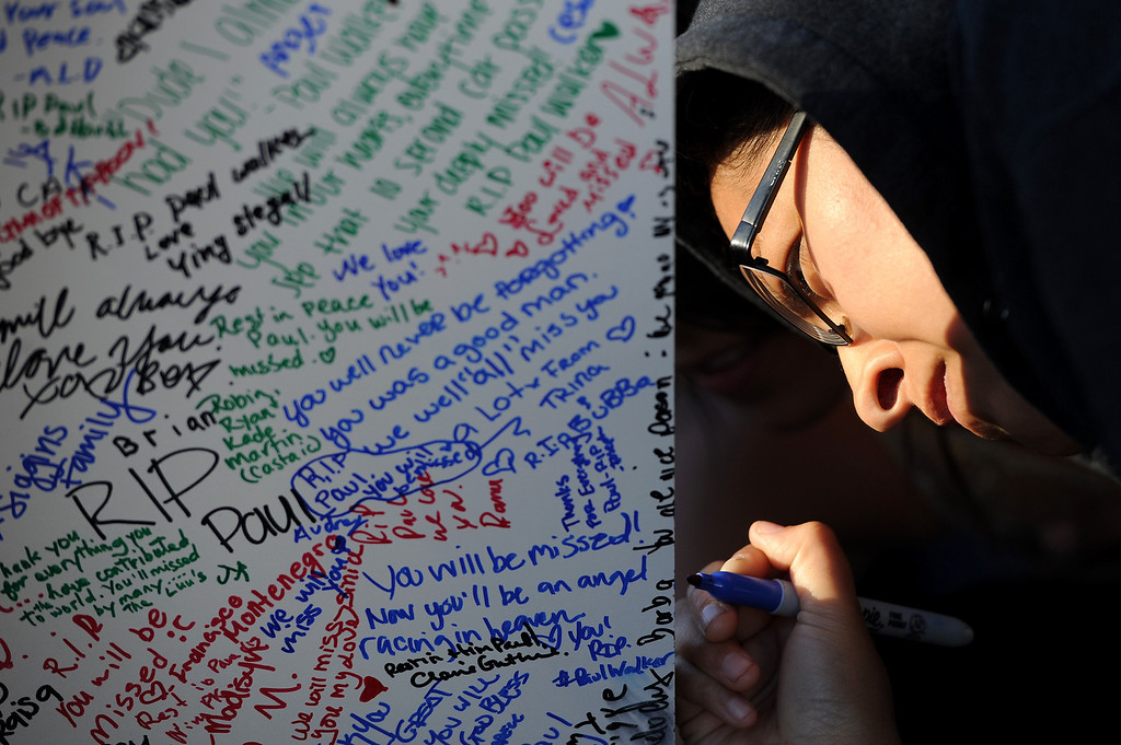 . Leticia Lopez signs a memorial for Paul Walker and Roger Rodas, Sunday, December 1, 2013, at the scene of their fatal crash site on Hercules Street near Kelly Johnson Parkway in Valencia. (Photo by Michael Owen Baker/L.A. Daily News)