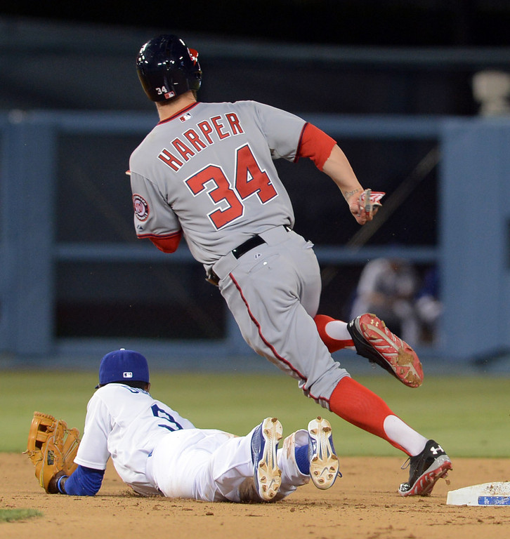 . Bryce Harper rounds second as Dodgers shortstop Dee Gordon lays on the ground after missing a throw from pitcher Javy Guerra May 13, 2013 in Los Angeles, CA.(Andy Holzman/Staff Photographer)