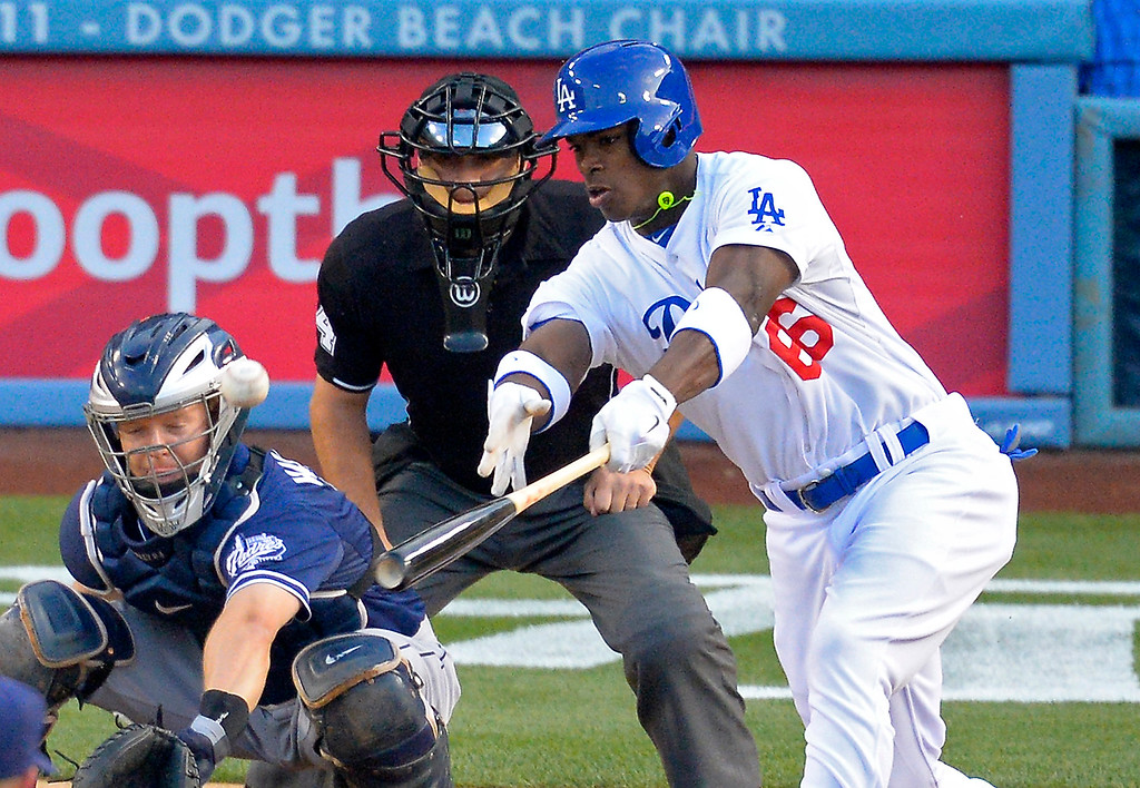 . Los Angeles Dodgers\' Yasiel Puig, right, hits a single as San Diego Padres catcher Nick Hundley catches during the first inning of their baseball game, Monday, June 3, 2013, in Los Angeles.  (AP Photo/Mark J. Terrill)