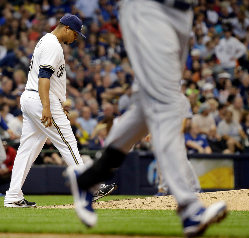 . Milwaukee Brewers starting pitcher Wily Peralta walks back to the mound after walking Los Angeles Dodgers\' Scott Van Slyke with the bases loaded during the second inning of a baseball game Wednesday, May 22, 2013, in Milwaukee. (AP Photo/Morry Gash)