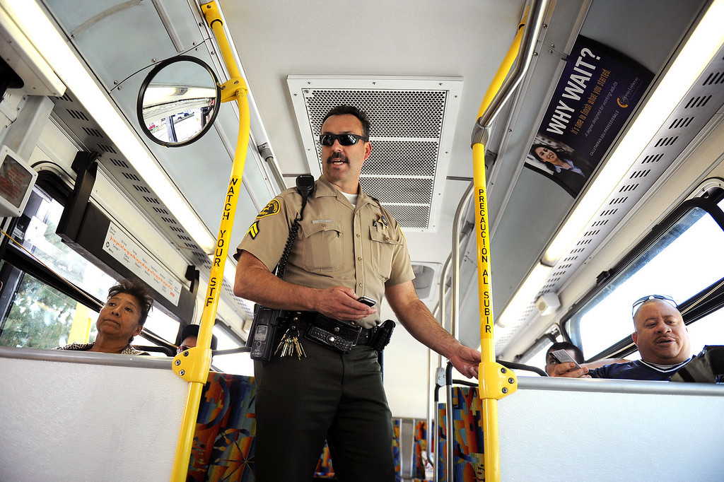 . LA County Sheriff deputy Dell Moore boards a bus to check riders TAP cards during an Orange Line fare enforcement operation at the Van Nuys Orange Line Station February 25, 2014.  Officials from Metro and the Los Angeles Sheriff\'s Department Transit Services Bureau announced a new two-pronged effort to cut down on fare-evaders on the Orange Line by improving communications and beefing up enforcement.(Andy Holzman/Los Angeles Daily News)