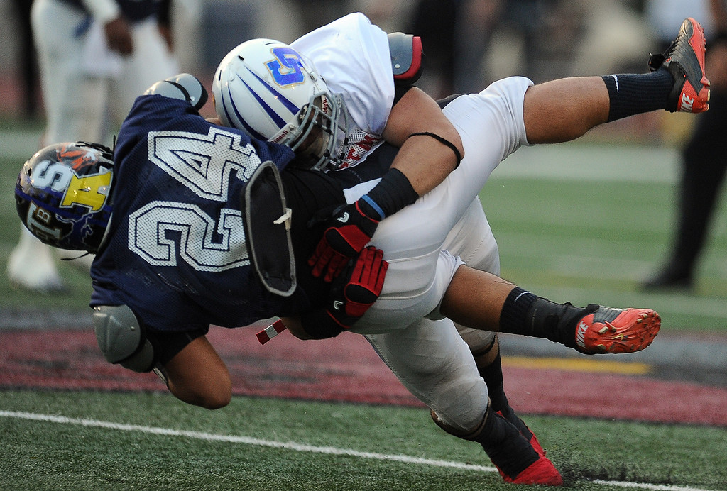 . East\'s Eric Ortiz (Charter Oak) tackles West\'s Roger Lemus (24) (Lincoln) for a loss of yards in the first half of the annual East vs. West San Gabriel Valley Hall of Fame all-star football game at West Covina High School on Friday, May 17, 2013 in West Covina, Calif.  (Keith Birmingham Pasadena Star-News)