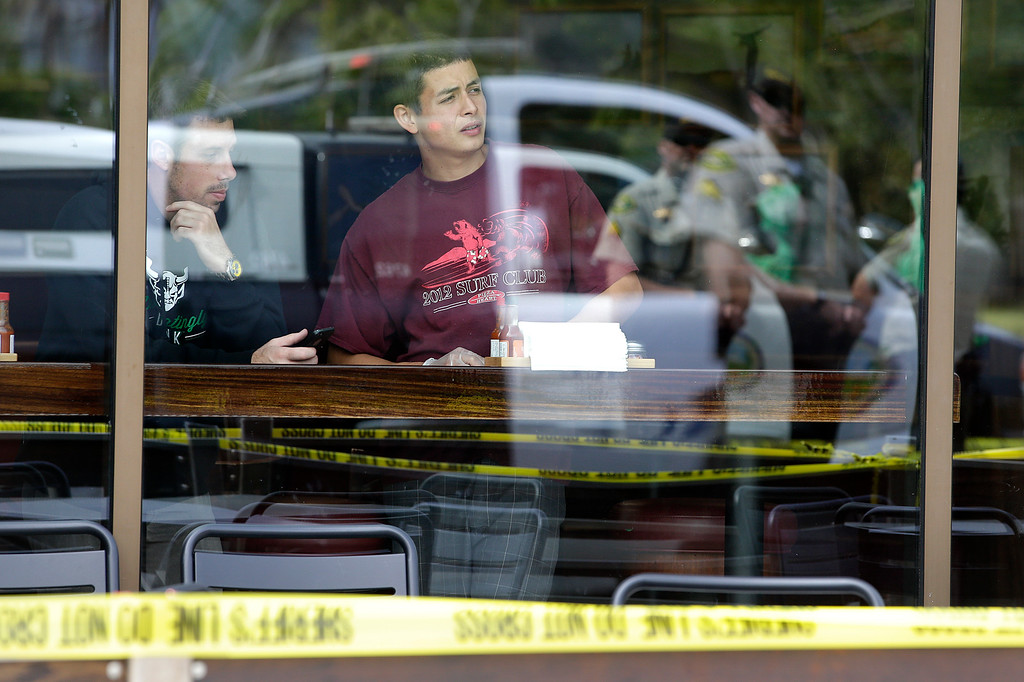 . Two men watch from a restaurant near the scene of a shooting on Saturday, May 24, 2014, in Isla Vista, Calif. A drive-by shooter went on a rampage near a Santa Barbara university campus that left seven people dead, including the attacker, and others wounded, authorities said Saturday. (AP Photo/Jae C. Hong)