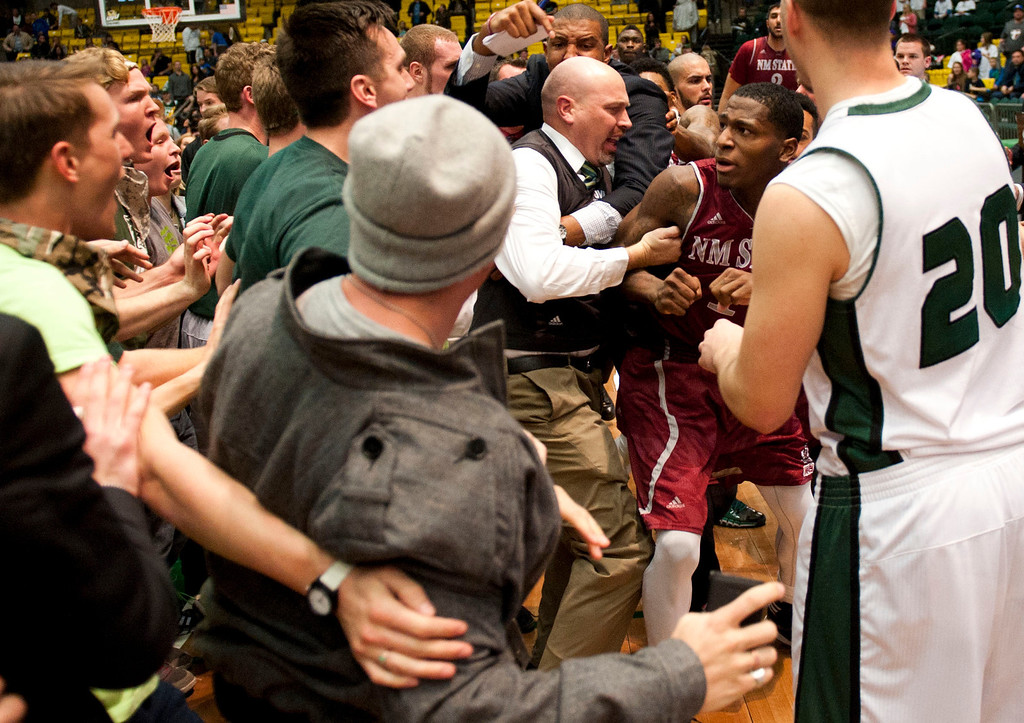 . In this Thursday, Feb. 27, 2014 photo, New Mexico State\'s DK Eldridge, at right center in red and white uniform,  is controlled by security during a brawl involving players and fans who came onto the court when New Mexico State guard K.C. Ross-Miller hurled the ball at Utah Valley\'s Holton Hunsaker seconds after the Wolverines\' 66-61 overtime victory against the Aggies.  (AP Photo/The Daily Herald, Grant Hindsley)