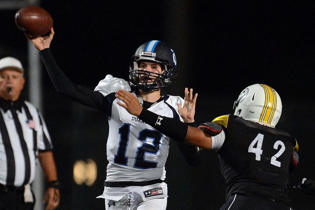 . Duarte quarterback Isaiah Scott (12) passes over Bassett\'s Brandon Garfias (42) in the first half of a prep football game at Bassett High School in La Puente, Calif., on Friday, Nov. 1, 2013.    (Keith Birmingham Pasadena Star-News)