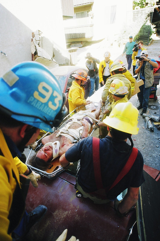 . Emergency workers remove a survivor from the first floor of Northridge Meadows.   Los Angeles Daily News file photo