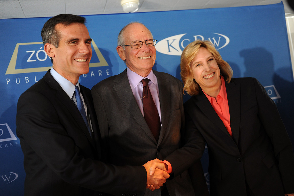 . Mayoral candidates Eric Garcetti and Wendy Greuel shake hands in front of moderator Warren Olney following their debate at the Peterson Automotive Museum in Los Angeles, Tuesday, May 7, 2013. (Michael Owen Baker/Staff Photographer)