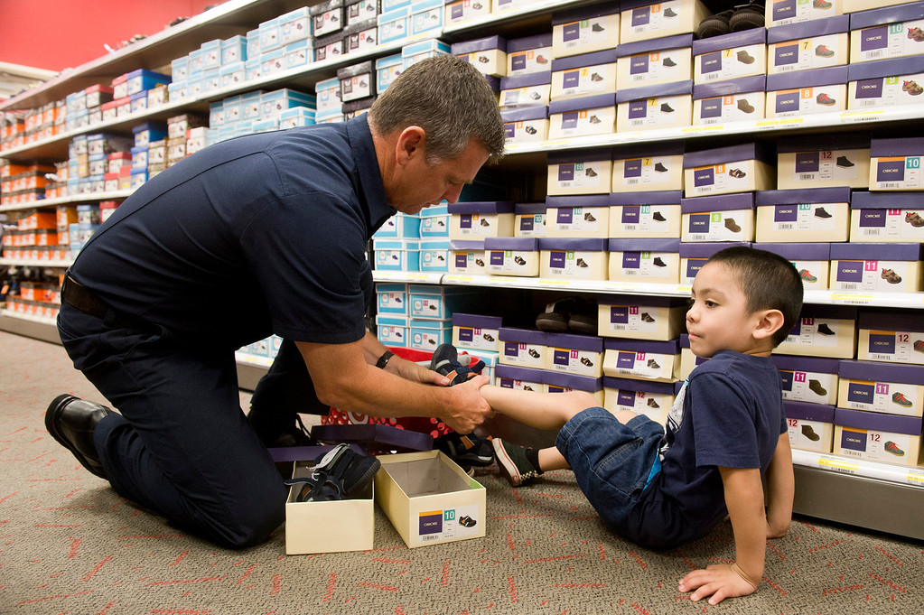 . LA County firefighter Bill Hailey helps 5-year-old Vincent Sanchez finds the a pair of shoes at Target in San Dimas on Tuesday, Sept. 10, 2013. Volunteers from the Soroptimists club, as well as the RSVP (retired senior volunteer patrol) of La Verne PD, Los Angeles County Sheriff\'s Department and Los County firefighters all paired up with a student from Bonita Unified elementary to take them shopping and find clothes and shoes. (Photo by Watchara Phomicinda/ San Gabriel Valley Tribune)