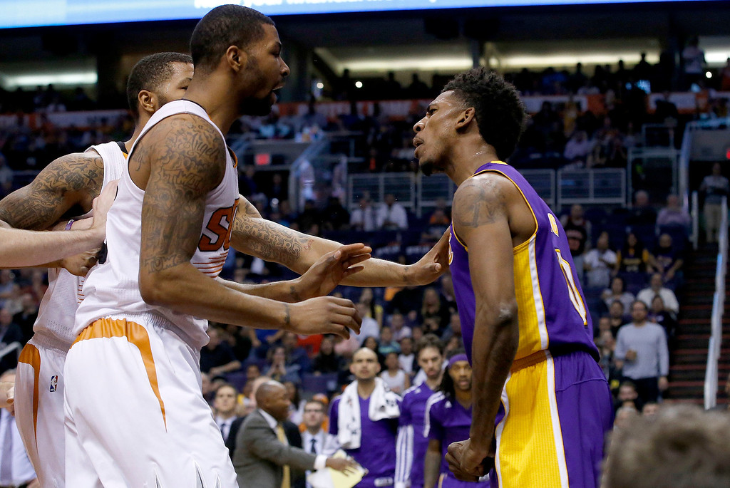 . Los Angeles Lakers\' Nick Young, right, has words with Phoenix Suns\' Marcus Morris and Markieff Morris, rear, during the first half of an NBA basketball game Wednesday, Jan. 15, 2014, in Phoenix. Young was ejected from the game along with Suns\' Alex Len. (AP Photo/Ross D. Franklin)