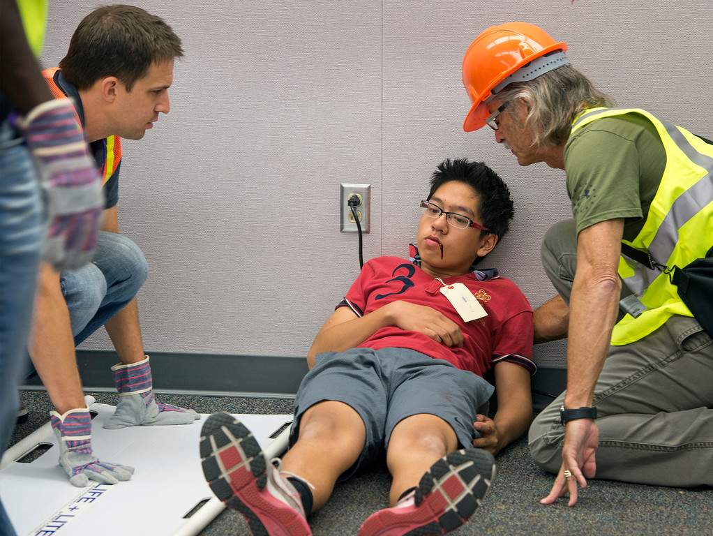 """. Diamond Bar High staff members Ryan Maine, left, and David Hamel evaluate an \""""injured\"""" student before taking him to triage during the Great ShakeOut earthquake drill at the Diamond Bar campus October 17, 2013.  (Staff photo by Leo Jarzomb/SGV Tribune)"""
