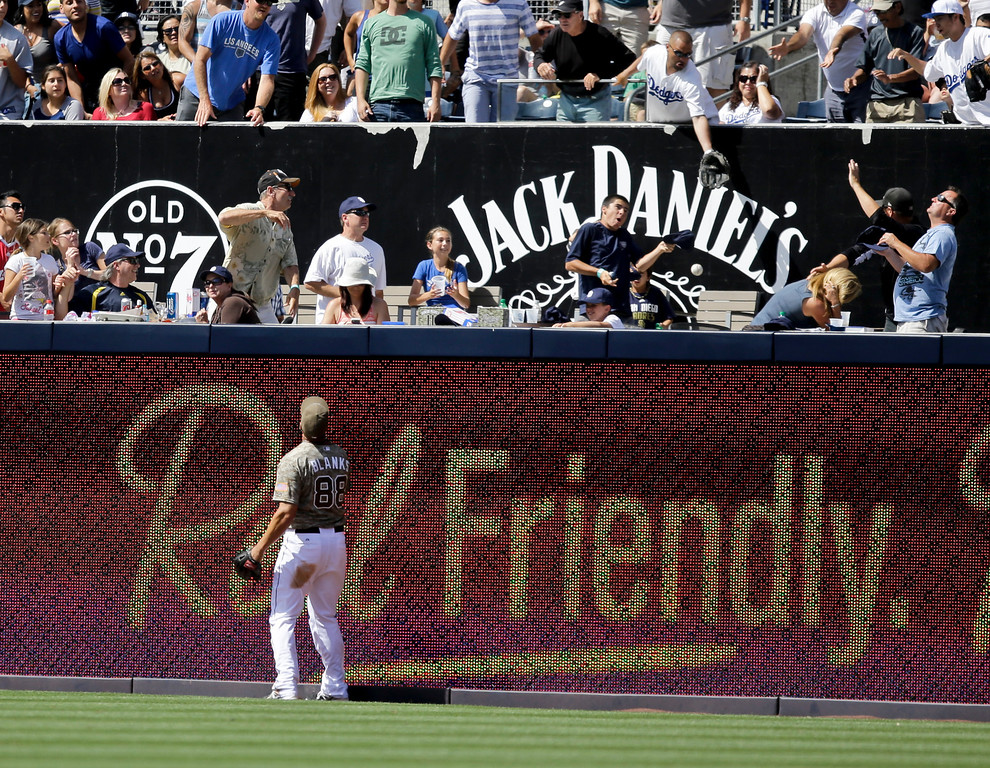 . San Diego Padres right fielder Kyle Blanks watches the ball sail over the fence as a fan misses the catch on a home run hit by Los Angeles Dodgers\' Adrian Gonzalez in the ninth inning of a baseball game in San Diego, Sunday, June 23, 2013. (AP Photo/Lenny Ignelzi)