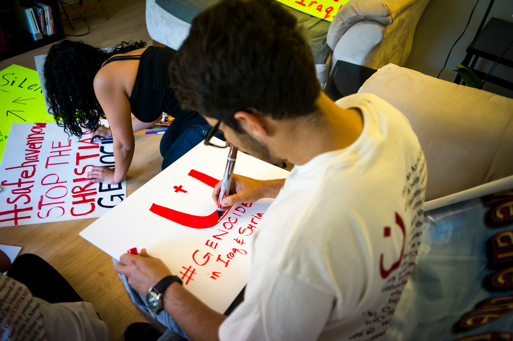 . Demil danipour of Northridge and Delilah George of North Hollywood prepare signs for a rally Saturday calling attention to the plight of christians being terrorized and killed in the middle east.   ( Photo by David Crane/Los Angeles Daily News )