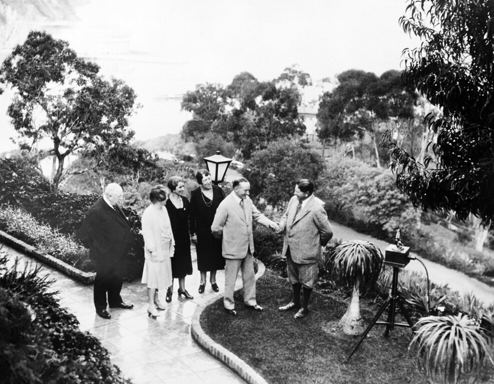 . Pres. Calvin Coolidge and Mrs. Grace Coolidge are shown on the grounds of the William Wrigley Jr. estate, Feb. 23, 1930, Catalina Island, Calif. Mr. Coolidge is shaking hands with Wrigley, behind them left to right are, George Reynolds, Mrs. Ada Wrigley, Mrs. Coolidge and Mrs. Reynolds. (AP Photo)