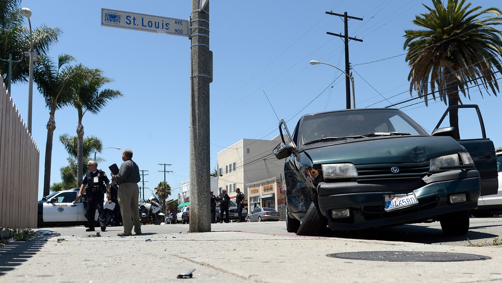 . Long Beach police investigate a police involved accident with a minivan at 10th Street and St. Louis Avenue in Long Beach July 30, 2013. The driver of the minivan suffered broken ribs the police officer was not injured. (Thomas R. Cordova/Staff Photographer)