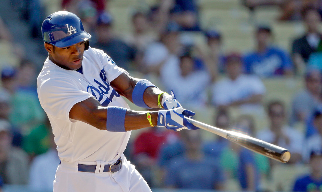 . Los Angeles Dodgers\' Yasiel Puig  follows through on a solo home run that gave the Dodgers a 1-0 win over the Cincinnati Reds in the 11th inning of a baseball game in Los Angeles, Sunday, July 28, 2013.  (AP Photo/Reed Saxon)