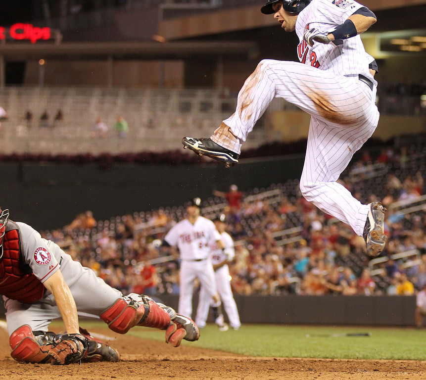 . Minnesota Twins Brian Dozier, left, slides safely into home base jumping over Los Angeles Angels catcher Chris Iannetta in the seventh inning of their baseball game in Minneapolis Monday, Sept. 9, 2013.(AP Photo/Andy Clayton-King)