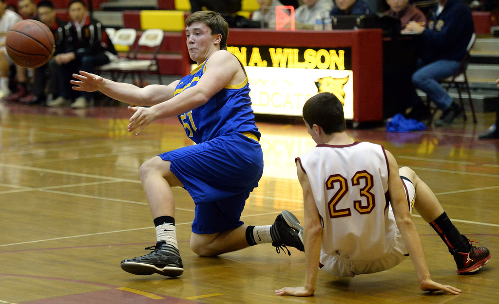 . San Dimas\' Josiah Erickson (51) passes a loose ball past Wilson\'s Erick Ramos (23) in the first half of a prep basketball game at Wilson High School in Hacienda Heights, Calif., on Friday, Jan. 31, 2014. (Keith Birmingham Pasadena Star-News)