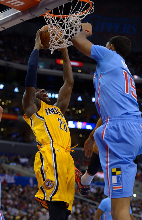 . Indiana Pacers center Ian Mahinmi, left, of France, puts up a shot as Los Angeles Clippers center Ryan Hollins defends during the first half of an NBA basketball game, Sunday, Dec. 1, 2013, in Los Angeles. (AP Photo/Mark J. Terrill)