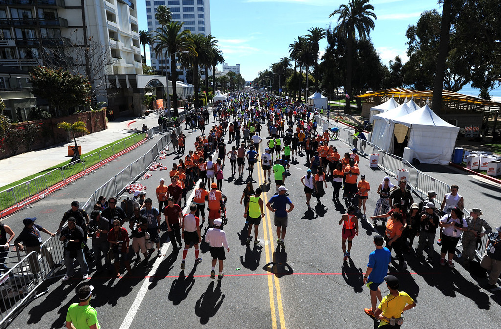 . Runners along Ocean Boulevard,  after crossing the finish line of  2014 ASICS LA Marathon finisher Bill Hopkins after feeling nauseous after he crossed the finish line in Santa Monica Calif,    Sunday, March 9,  2014. 