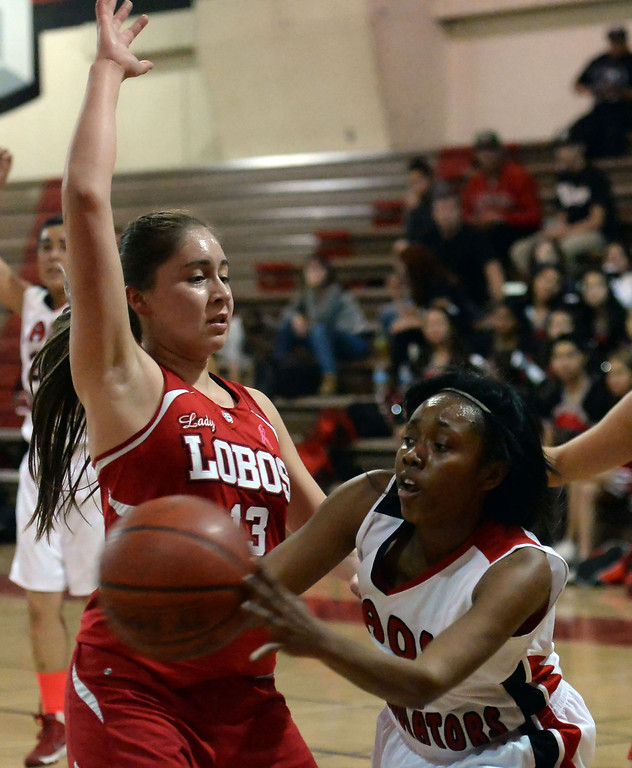 . Gladstone\'s Tiara Rice (11) passes past Workman\'s Indelisa Bernal (13) in the first half of a prep basketball game at Gladstone High School in Covina, Calif., on Friday, Jan. 17, 2014. (Keith Birmingham Pasadena Star-News)