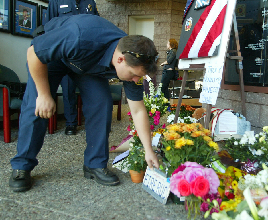 . Novato firefighter Mathew Topping places fallen firefighter Steven Rucker\'s license plate at a memorial at his firehouse in Novato, Calif., Thursday Oct. 30, 2003. Rucker was killed Wednesday, while battling the Cedar Fire in Southern California. (AP Photo/George Nikitin)
