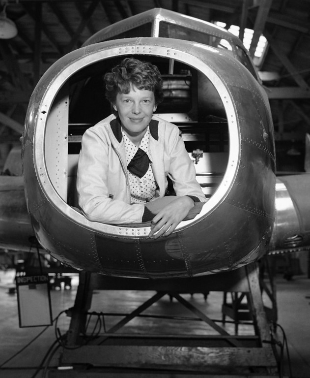 . Amelia Earhart, noted fier, inspected the Twin-Engined Lockheed Electra Monoplane which is being built for her use in future long distance flights at the plant, May 26, 1936, Burbank, Calif. The ship will carry 1200 gallons of gasoline and have a cruising range of more than 4500 miles. Photo shows Miss Earhart in plane looking over blueprints. (AP Photo)