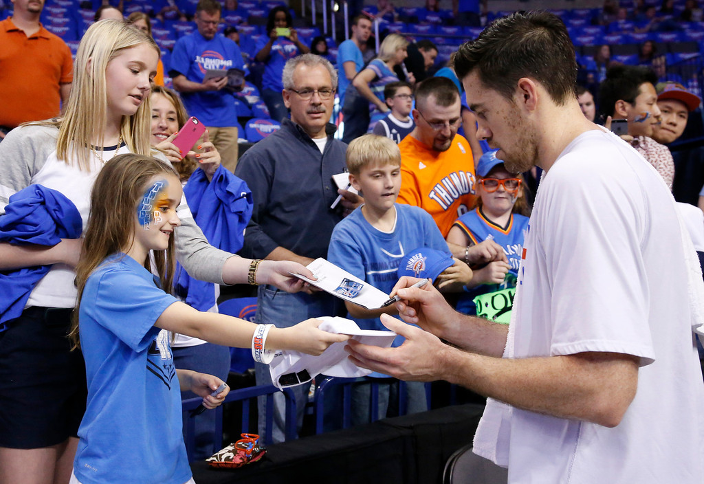 . Oklahoma City Thunder forward Nick Collison, right, signs autographs for fans before the start of Game 1 of the Western Conference semifinal NBA basketball playoff series in Oklahoma City, Monday, May 5, 2014. (AP Photo/Sue Ogrocki)