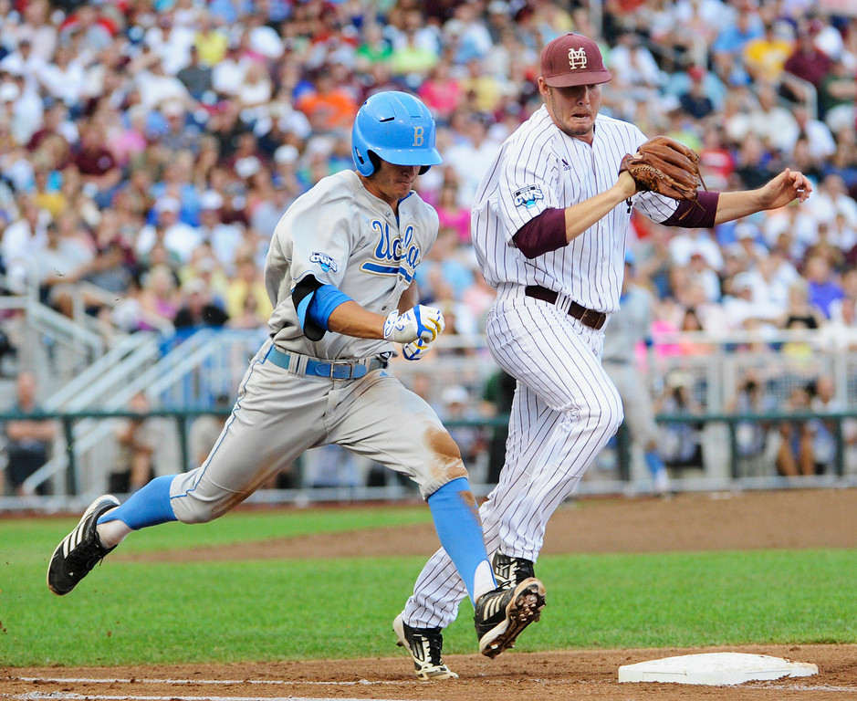 . Mississippi State pitcher Chad Girodo, right, and  UCLA base runner Kevin Kramer race for first base in the second inning of Game 1 of the NCAA College World Series best-of-three finals, Monday, June 24, 2013, in Omaha, Neb. Kramer was out on the play. (AP Photo/Francis Gardler)