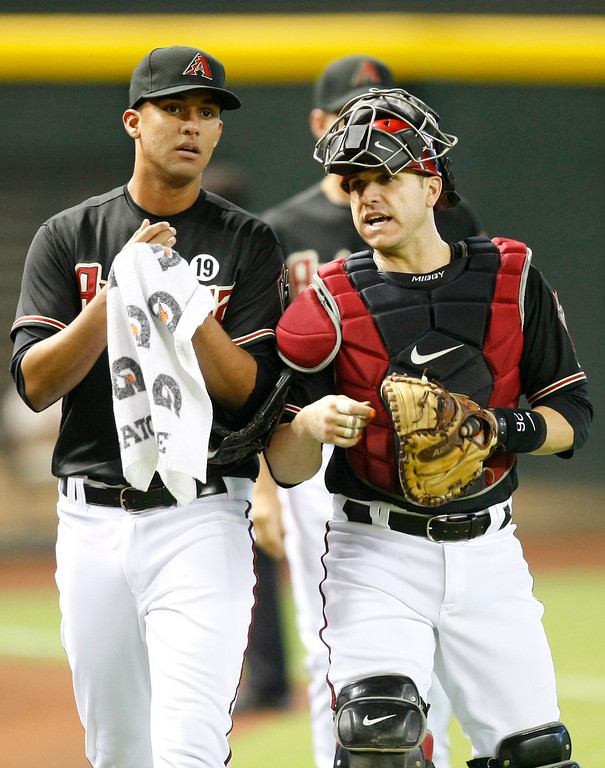 . Arizona Diamondbacks pitcher Randall Delgado (48), left, and Miguel Montero (26) before a baseball game against the Los Angeles Dodgers on Monday, July 8, 2013, in Phoenix. (AP Photo/Rick Scuteri)