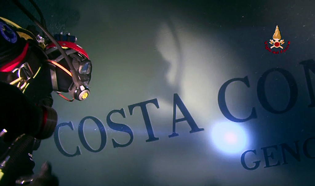 . In this undated photo released by Italian Fire Brigades, Vigili del Fuoco, with its official logo at top right Tuesday, Jan. 31, 2012, a fireman scuba diver checks the hulk of the luxury cruise ship Costa Concordia that run ashore off the Tuscany island of Isola del Giglio, Italy. Italian emergency officials are ending the search for missing people in the submerged part of the Costa Concordia cruise ship due to the danger to rescue workers. Italy\'s Civil Protection agency said Tuesday that technical studies indicated the deformed hull of the ship created too many safety concerns to continue the search within it. (AP Photo/Vigili del Fuoco)