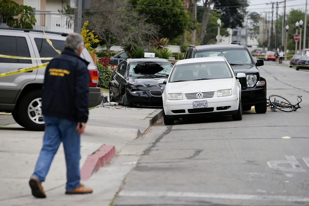 . An investigator walks toward a black BMW sedan driven by a drive-by shooter on Saturday, May 24, 2014, in Isla Vista, Calif. The shooter went on a rampage near a Santa Barbara university campus that left seven people dead, including the attacker, and seven others wounded, authorities said Saturday. (AP Photo/Jae C. Hong)