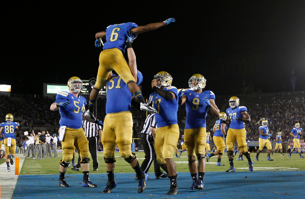 . UCLA RB Jordon James is hoisted up after his 27-yard touchdown run in the third quarter against Nevada, Saturday, August 31, 2013, at the Rose Bowl. (Michael Owen Baker/L.A. Daily News)