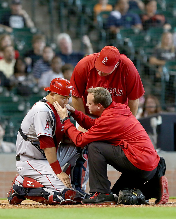 . HOUSTON, TX - SEPTEMBER 15: Trainers look at Hank Conger #16 of the Los Angeles Angels of Anaheim after taking a ball to the face against the Houston Astros in the ninth inning on September 15, 2013 at Minute Maid Park in Houston, Texas. (Photo by Thomas B. Shea/Getty Images)