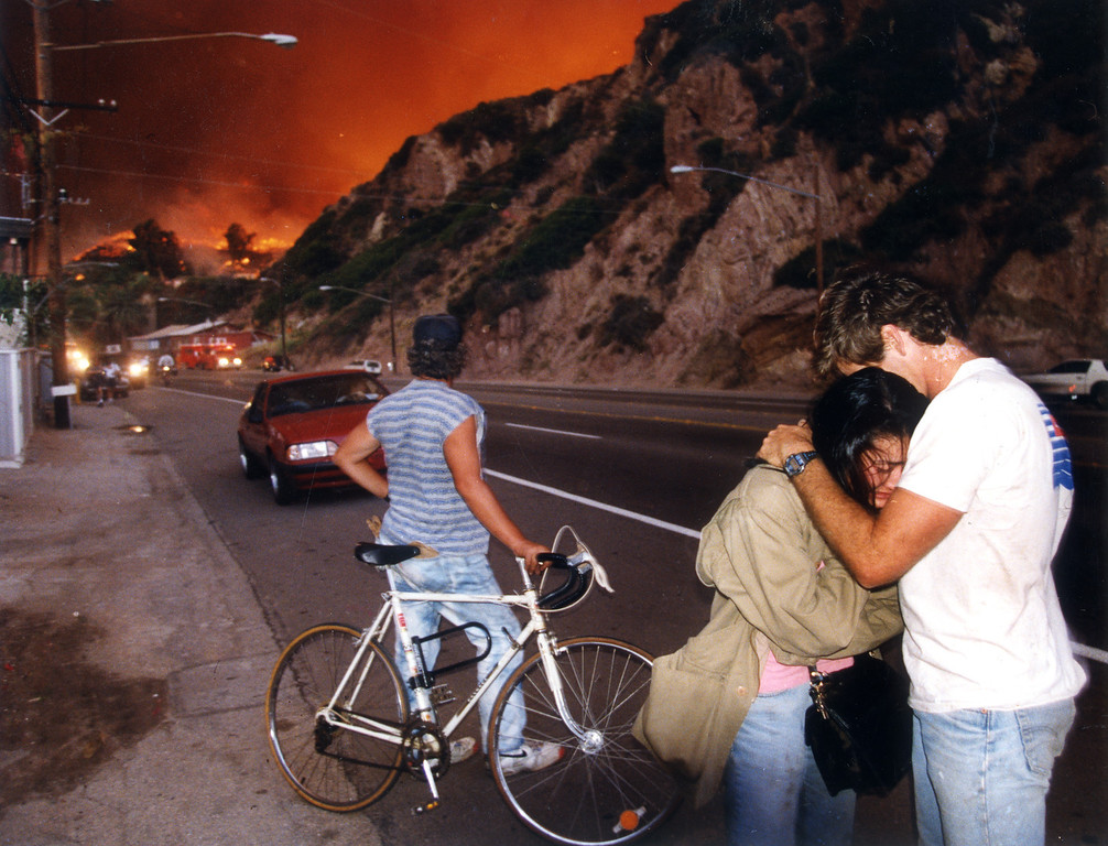 . Lori Shishino hugs Lee Brooks after being rescued by firefighters. The couple had gone back for their dog, which had run into the flames. (11/2/93)   Los Angeles Daily News file photo