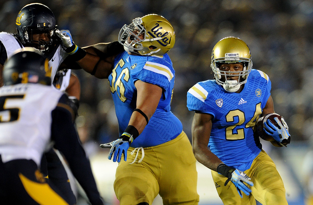 . UCLA running back Paul Perkins (24) runs around the block for a first down against California during the first half of their college football game in the Rose Bowl in Pasadena, Calif., on Saturday, Oct. 12, 2013.   (Keith Birmingham Pasadena Star-News)