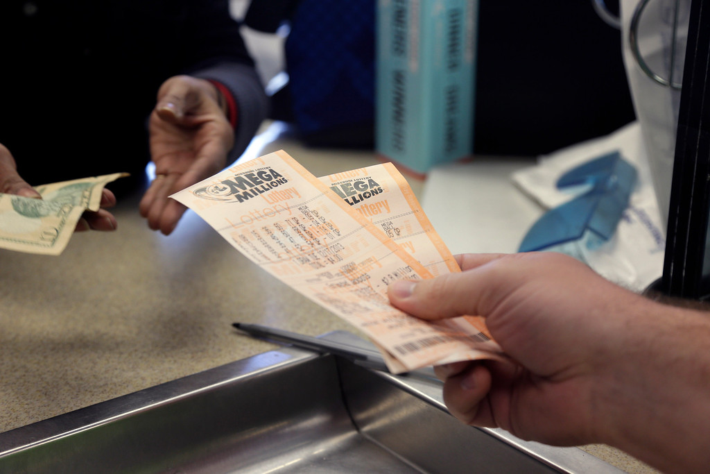 . Scott Hoormann buys two Mega Millions lottery tickets at Energy Express Monday, Dec. 16, 2013, in St. Louis. The Mega Millions jackpot now stands at an estimated $586 million with the next drawing set for Tuesday night. (AP Photo/Jeff Roberson)