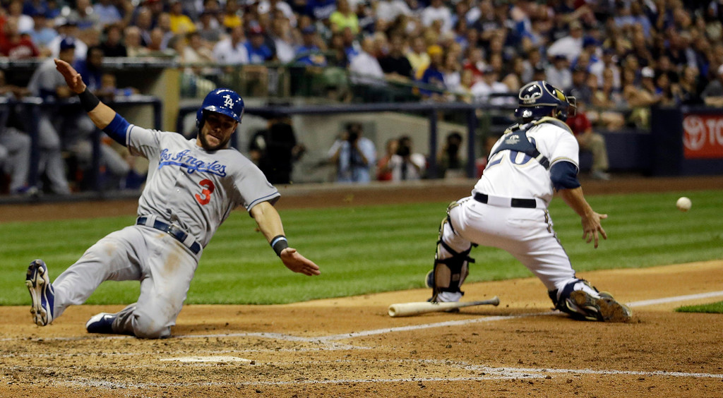 . Los Angeles Dodgers\' Skip Schumaker slides safely home past Milwaukee Brewers catcher Jonathan Lucroy during the fourth inning of a baseball game Tuesday, May 21, 2013, in Milwaukee. Schumaker scored from second on a hit by Zack Greinke. (AP Photo/Morry Gash)